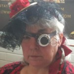 Charlotte Babb with steampunk monocle and wire teacup with red ribbon.